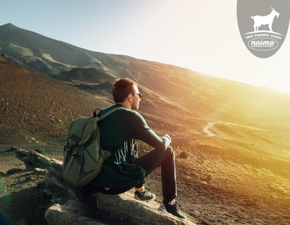 Man vacation sitting rock seeing mountain sunset [susukambing.id]